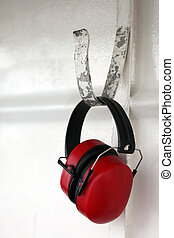 Hearing protection - A pair of earmuffs hanging from a hook