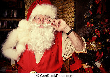 christmastime - Santa Claus standing at home with gifts,...