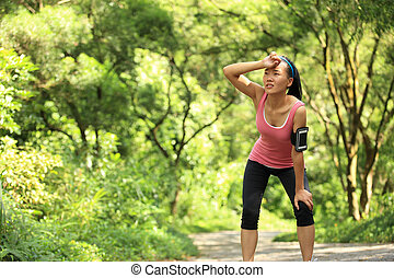 tired female runner taking a rest after running hard in...