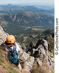 Climbing sport: caucasian young boy takes a rest observing...