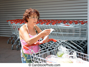 woman pushing a shopping caddy on parking of supermarket