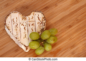 Neufchatel cheese shaped like heart with grapes on wooden...