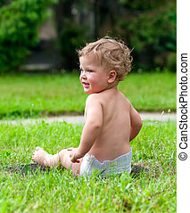 little curly-headed child is sitting on the green grass
