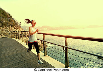 woman running seaside board walk