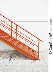 Red metal stairs on the outside, detail of a staircase on a...