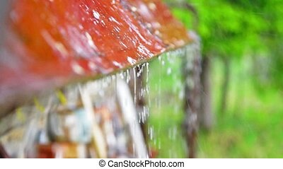 Cottage roof under heavy rain - Rain drops running down the...