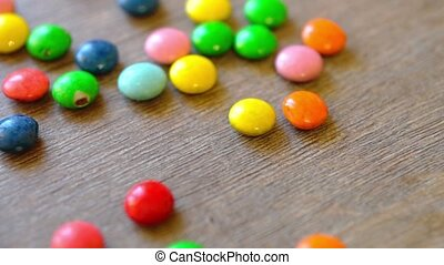Wooden table with falling candies - Colorful candies...