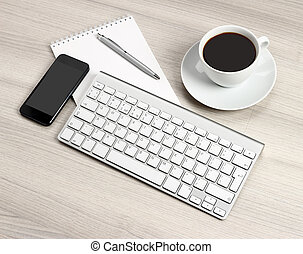 Computer desk with a cup of coffee, a notebook and pen
