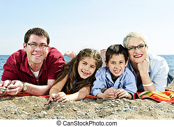 Happy family at beach - Happy family laying on towel at...