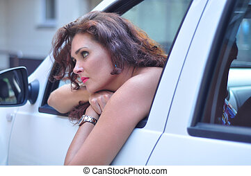 woman in white car looking bored - Portrait of young...