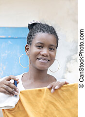 Afro beauty drying her clothes - Young Afro beauty drying...