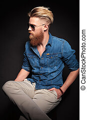 red beard man sitting with his hand in the pocket