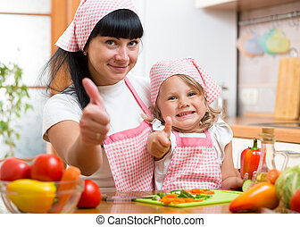 Kid girl and mother cooking and showing thumb up