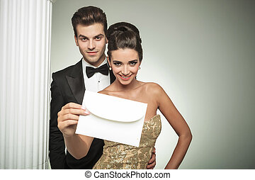 happy young couple presenting an invite to their wedding,...