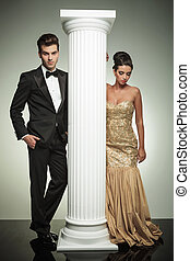 attractive elegant couple posing near column in studio,...