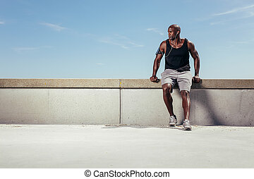 Male runner relaxing on embankment looking away copyspace -...