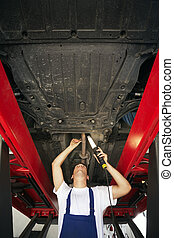 mechanic standing under car engine and holding lamp Copy...