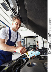 mechanic - side view of mechanic checking motor oil...