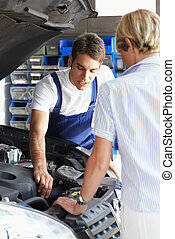 mechanic talking with female client in auto repair shop.