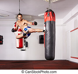 Jump kick - Kickboxer deploying a jump kick on a punchbag in...
