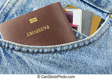 Closeup of credit card and passport in jeans in blue denim...