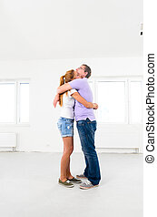 new apartment - happy couple is embracing at their new empty...