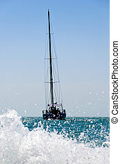 yacht drifting in the sea with sails down. Splash of water...
