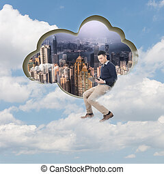 Cloud concept with man sit at a cloud shaped wall and using...