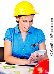 Portrait of young woman with hard hat - Serious female with...