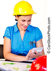 Portrait of young woman with hard hat - Smiling female with...