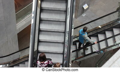 Escalators at the mall - people go up the escalator at the...