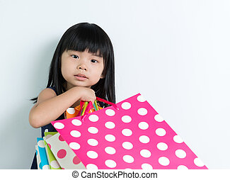Child with shopping bags - Little Asian girl holding...