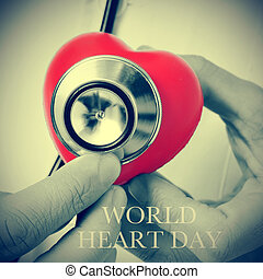 world heart day - closeup of a doctor auscultating a red...
