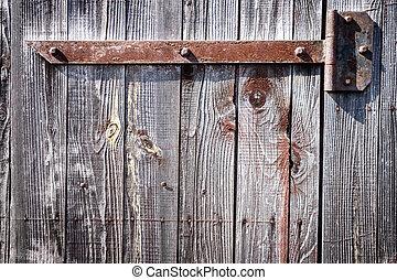 Iron hinge on door - Rusty aged iron hinge on old wooden...