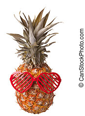 Heart shaped plastic sunglasses on pineapple - Close-up of...