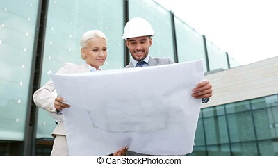 smiling businessmen with blueprint and helmets - business,...