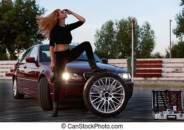 Young pretty lady with a clasic car