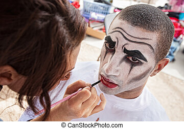 Circus Clown Makeup - Makeup artist lining lips of male...