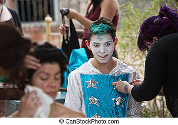 Cheerful Performer with Green Hair - Makeup artist dressing...