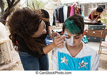 Clown Getting Makeup - Female makeup artist putting makeup...
