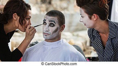 Clown Getting Eye Shadow - Handsome male clown with stylist...