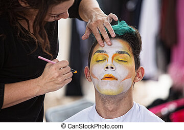 Sylist Putting Makeup on Clown - Young male clown getting...