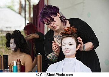 Stylist Fixing Hair - Stylist with tattoo fixing hair for...