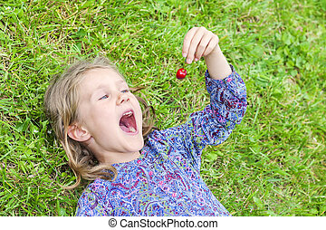 girl lying on the grass with cherry - little girl lying on...