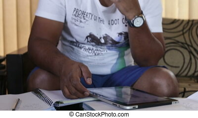 man typing on the tablet while sitting on a sofa