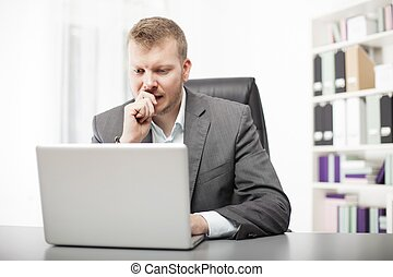 Concerned businessman working at his desk in the office...