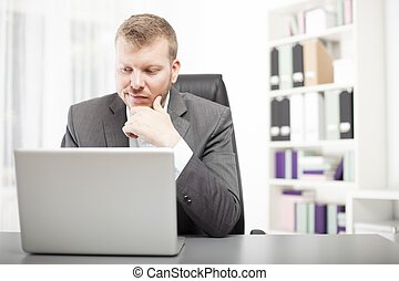 Man looking at his laptop with a wry expression -...