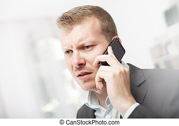 Anxious businessman taking a mobile call - Anxious...