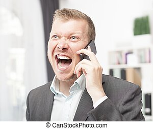 Exuberant young man shouting in reaction to a call -...
