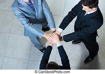 symbol of teamwork - team of three businessmen clasped her...